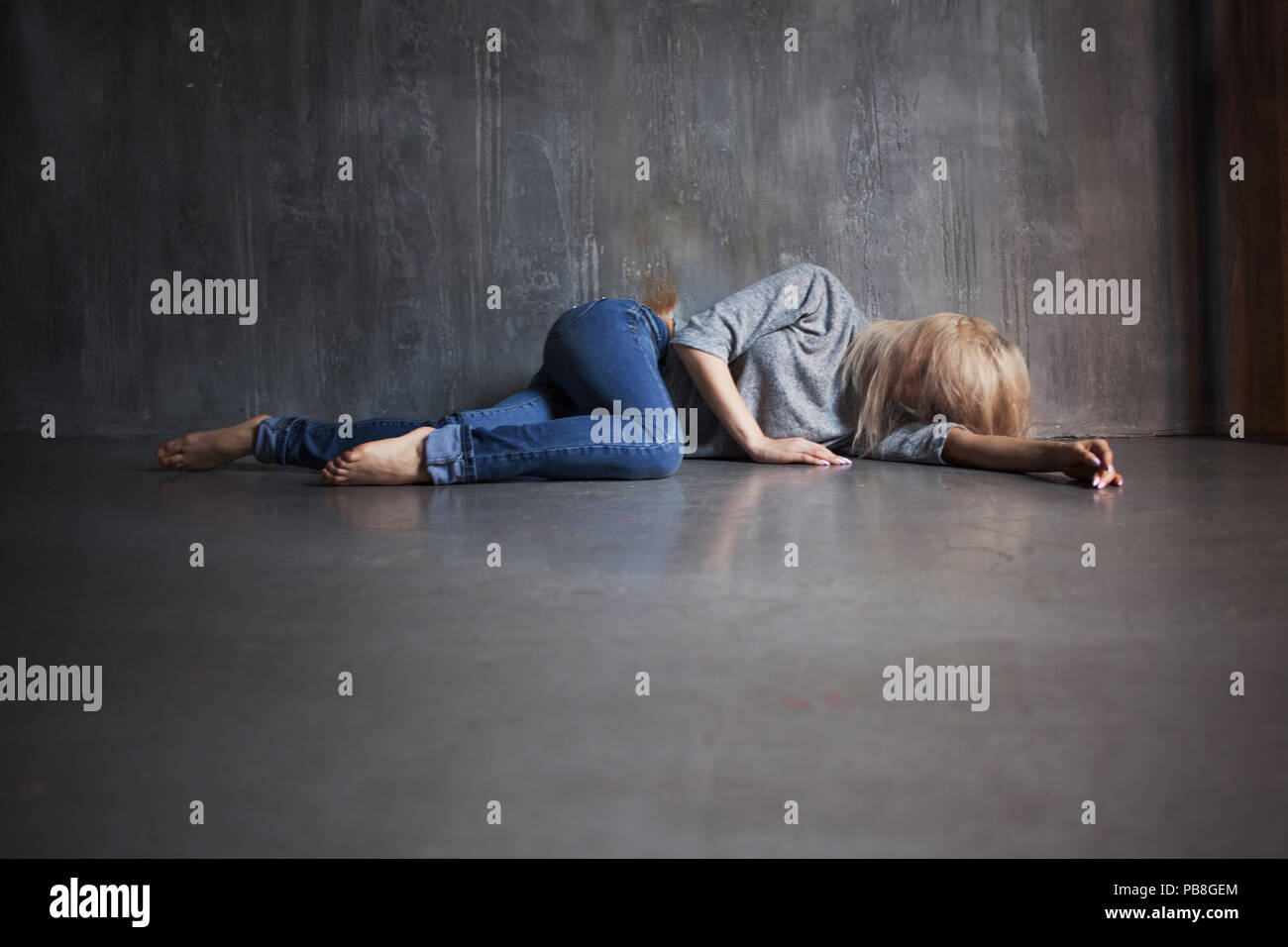 Mental health. Young woman lying on the floor, concept of stress or post-traumatic disorder - Stock Image