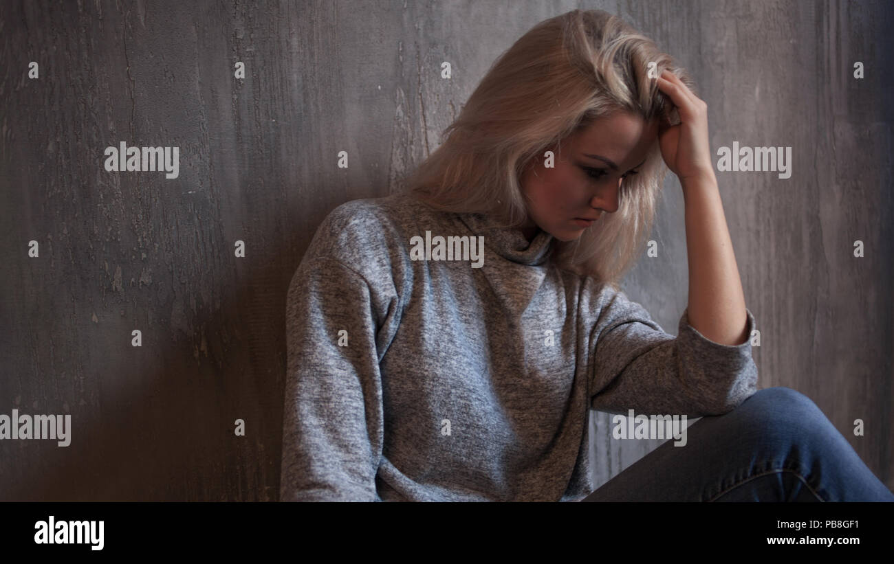 chronic fatigue syndrome. Young woman tired. Depressed girl sitting on the floor, gray background - Stock Image