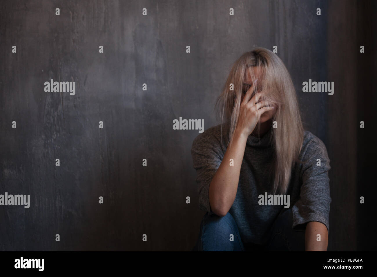 chronic fatigue syndrome. Young woman, palm on the face. Depressed girl sitting on the floor, gray background - Stock Image