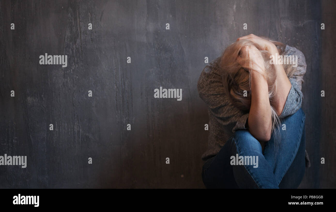 Depression, abuse. Woman sitting with hands on her head. Gray background, copy space - Stock Image