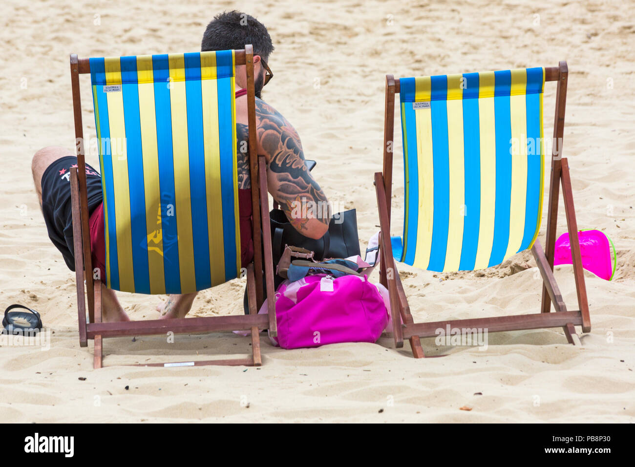 Bournemouth, Dorset, UK. 27th July 2018. UK weather: Sunseekers head to the seaside to soak up the sun at Bournemouth beaches on a warm humid day with some cloud cover. Man with tattoos sitting in deckchair. Credit: Carolyn Jenkins/Alamy Live News - Stock Image