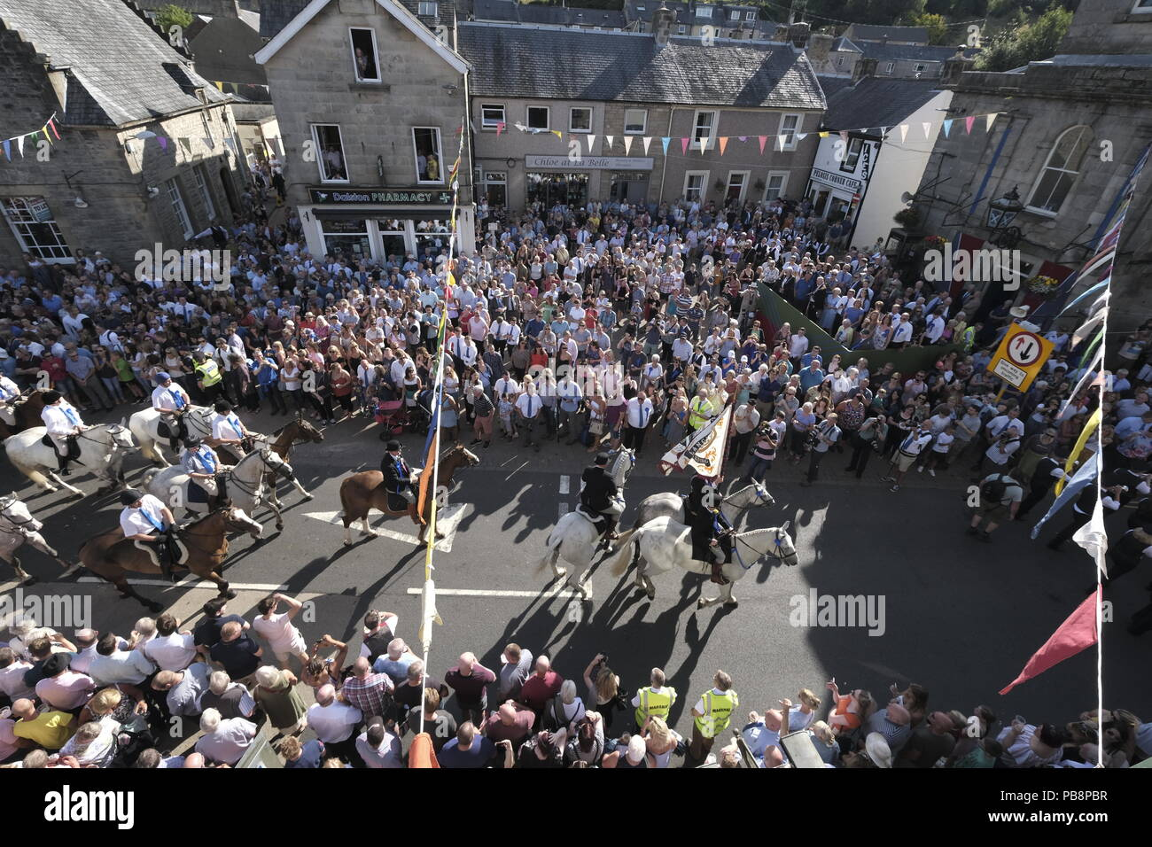 Langholm, Scotland, UK. 27th July, 2018.   Langholm Common Riding - 'Langholm's Great Day' the mounted supporters led by Langholm Cornet Iain Little and his Right-hand man Stuart Murray and Left-hand man Simon Tweddle passing thru the Market Square in Langholm, 'The Muckle Toon' has seen tradition upheld for over 250 years with the Annual Langholm Common Riding which takes place every year on the last Friday in July, This year falling on Friday 27th.    Credit: Rob Gray/Alamy Live News - Stock Image