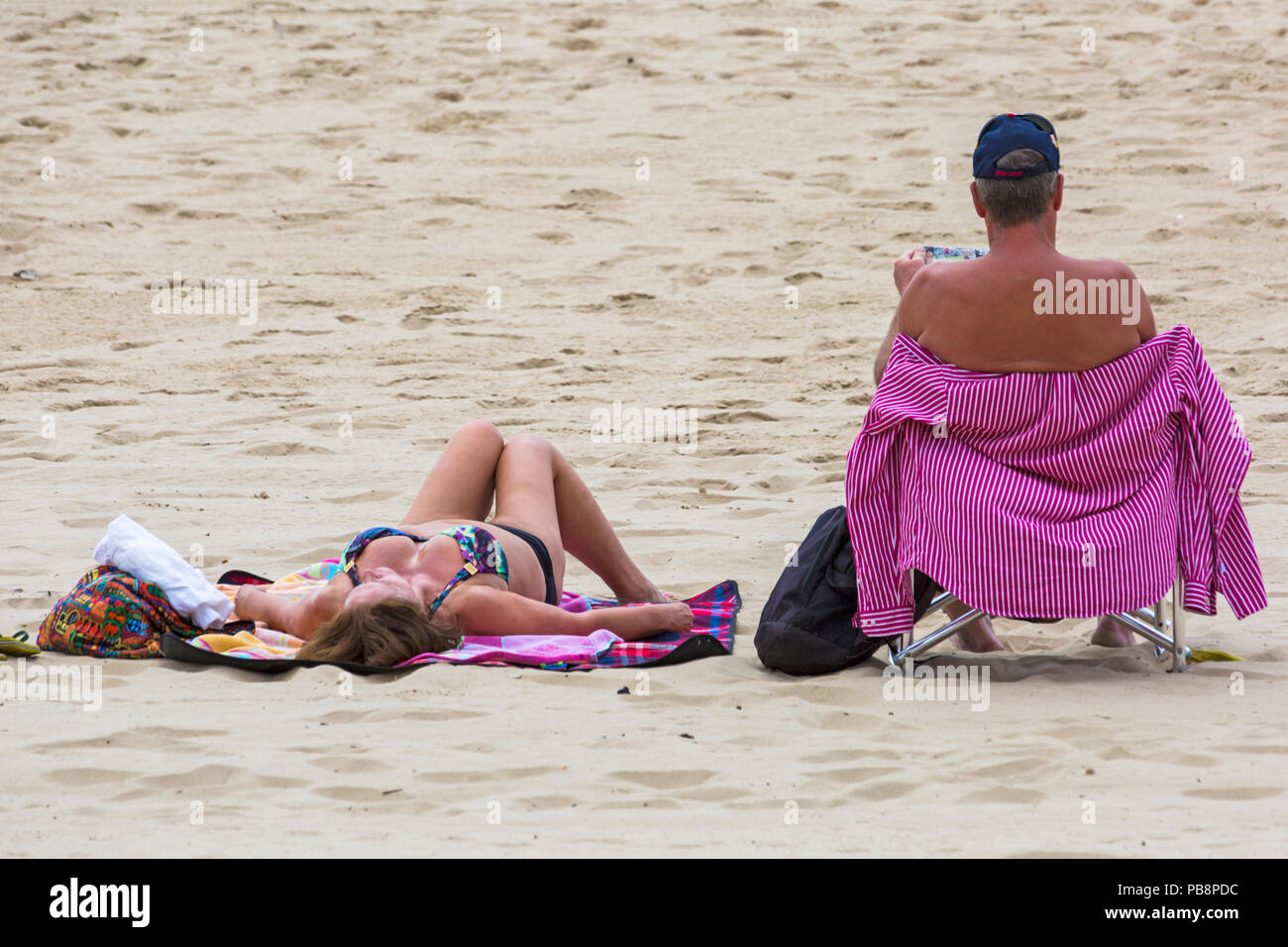 Bournemouth, Dorset, UK. 27th July 2018. UK weather: Sunseekers head to the seaside to soak up the sun at Bournemouth beaches on a warm humid day with some cloud cover. Couple sunbathing on the beach. Credit: Carolyn Jenkins/Alamy Live News - Stock Image