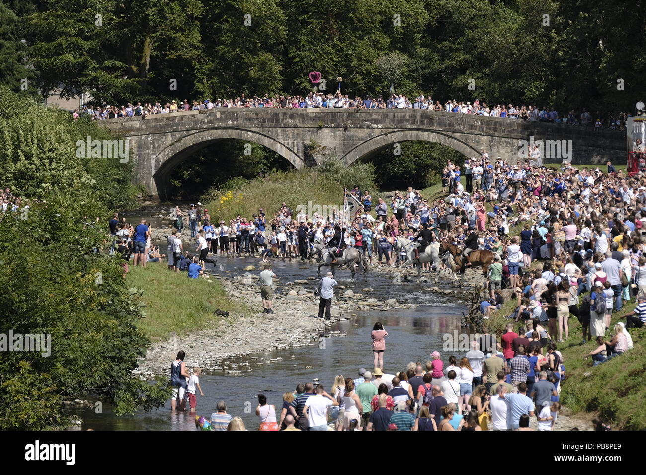 Langholm, Scotland, UK. 27th July, 2018.  Langholm Common Riding - 'Langholm's Great Day' the mounted supporters led by Langholm Cornet Iain Little and his Right-hand man Stuart Murray and Left-hand man Simon Tweddle fording the Ewes Water ahead of the cavalcade onto the Castleholm in Langholm, 'The Muckle Toon' has seen tradition upheld for over 250 years with the Annual Langholm Common Riding which takes place every year on the last Friday in July, This year falling on Friday 27th.   Credit: Rob Gray/Alamy Live News - Stock Image