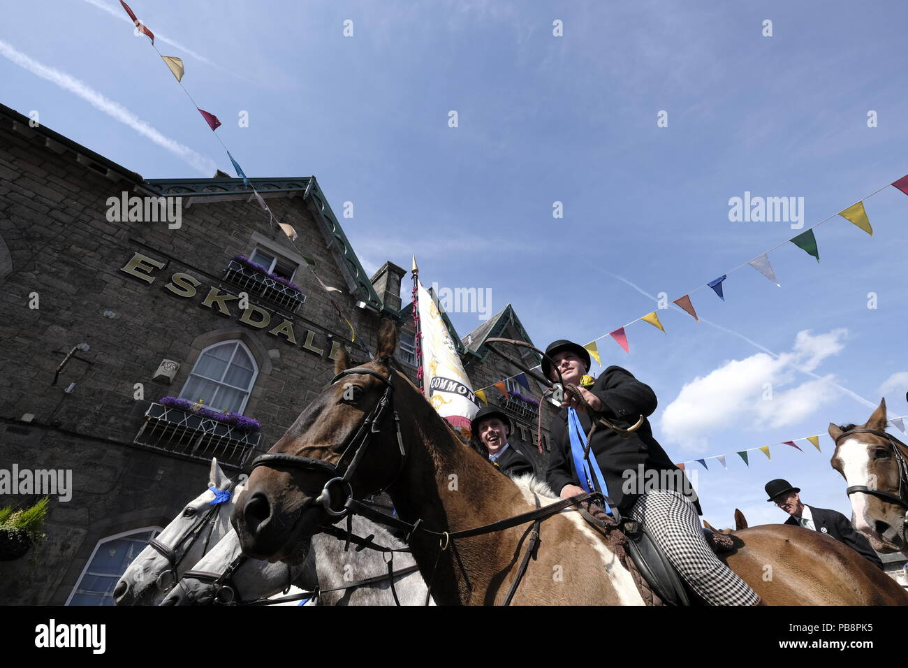 Langholm, Scotland, UK. 27th July, 2018.    Langholm Common Riding - 'Langholm's Great Day' Langholm Cornet Iain Little with his Left-hand man Simon Tweddle and Right-hand man Stuart Murray tasing the Eskdale Hotel in Langholm, 'The Muckle Toon' has seen tradition upheld for over 250 years with the Annual Langholm Common Riding which takes place every year on the last Friday in July, This year falling on Friday 27th.   Credit: Rob Gray/Alamy Live News - Stock Image
