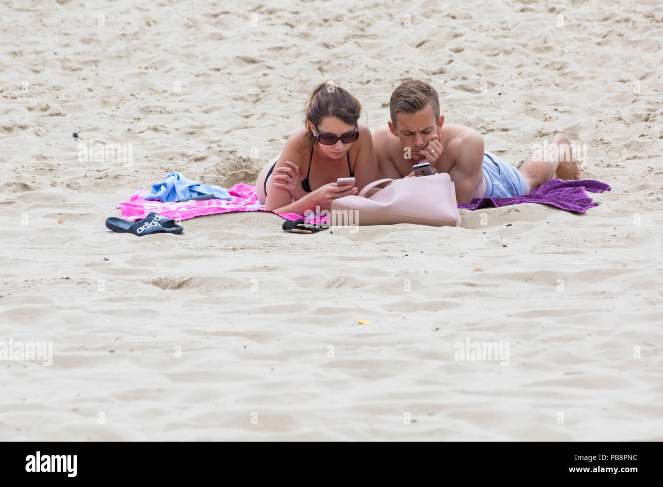 Bournemouth, Dorset, UK. 27th July 2018. UK weather: Sunseekers head to the seaside to soak up the sun at Bournemouth beaches on a warm humid day with some cloud cover. Couple sunbathing on beach looking at mobile phones iphones smartphones. Credit: Carolyn Jenkins/Alamy Live News - Stock Image