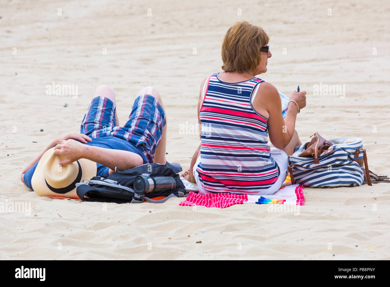 Bournemouth, Dorset, UK. 27th July 2018. UK weather: Sunseekers head to the seaside to soak up the sun at Bournemouth beaches on a warm humid day with some cloud cover. Mature couple relaxing on the beach. Credit: Carolyn Jenkins/Alamy Live News - Stock Image