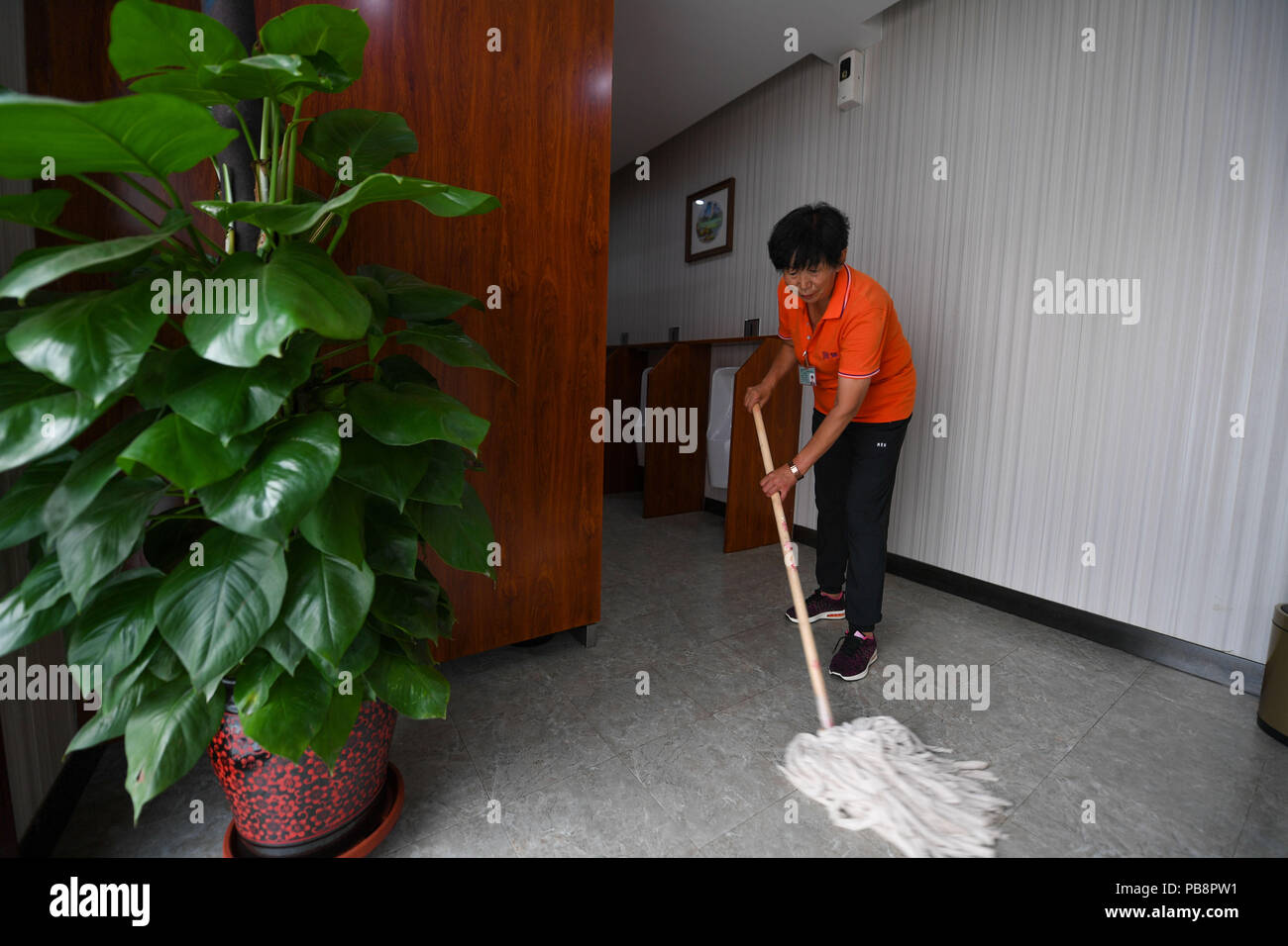 180727) -- HOHHOT, July 27, 2018 (Xinhua) -- A cleaner works at an ...