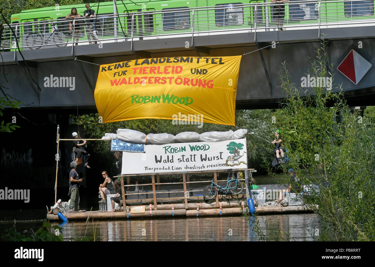 27 July 2018, Germany, Hanover: A raft of the environmental and nature conservation organisation Robin Wood floating on the Ihme River with tour participants. In the background, climbing activists let themselves down the Benno Ohnesorg Bridge with a protest banner reading: 'No state funding for animal suffering and forest destruction!' Under the motto: 'Forest instead of sausage - drastically reduce animal production' Robin Wood has started this year's raft action tour in the capital of Lower Saxony. Over the next three weeks the crew will sail on the wooden raft via the Mittelland Canal and W - Stock Image