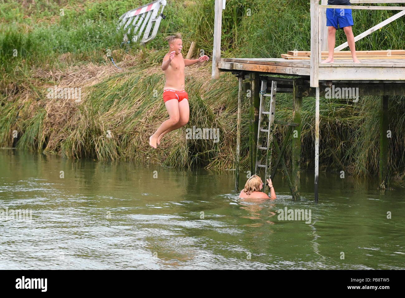 Young people wearing only shorts jumping into a river during the Summer 2018 heatwave in West Sussex, England, UK. - Stock Image