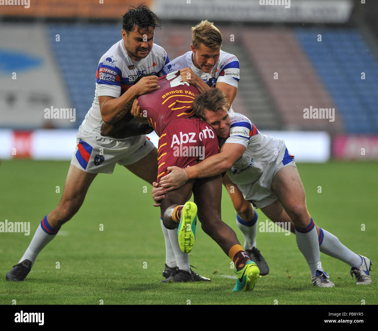 Wakefield, UK. 27th July 2018. John Smiths Stadium, Huddersfield, UK. 27th July, 2018. Betfred Super League Rugby League between Huddersfield Giants and Wakefield Trinity; Huddersfield Giants' Jermaine McGillvary is stopped by Justin Horo, Jacob Miller and Matty Ashurst.  Dean Williams Credit: Dean Williams/Alamy Live News - Stock Image