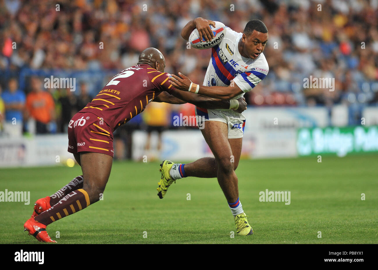 Wakefield, UK. 27th July 2018. John Smiths Stadium, Huddersfield, UK. 27th July, 2018. Betfred Super League Rugby League between Huddersfield Giants and Wakefield Trinity; Reece Lyne of Wakefield Trinity shrugs of Huddersfield Michael Lawrence.  Dean Williams Credit: Dean Williams/Alamy Live News - Stock Image