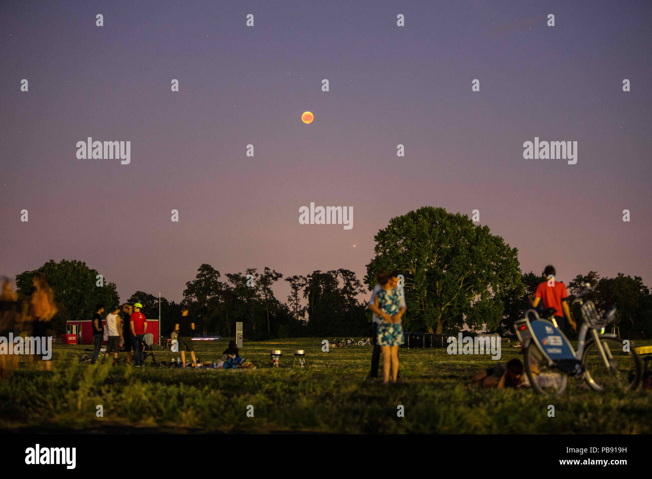 Berlin, Berlin, Germany. 27th July, 2018. People gather at Tempelhofer Feld park to watch the moon glows in a red color during a full lunar eclipse over Berlin, Germany on July 27 2018. The phenomenon also known as 'Blood moon' was well observed all across Germany when the moon was covered by Earth's shade. It is also reported that it will be the longest total lunar eclipse of the 21st century. Credit: Omer Messinger/ZUMA Wire/Alamy Live News - Stock Image