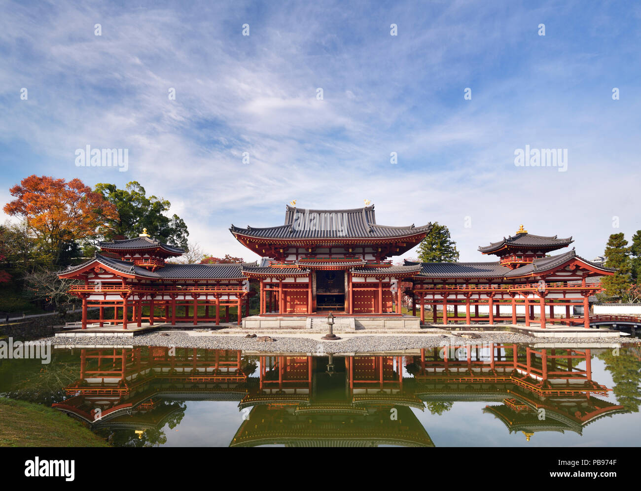 Beautiful Phoenix Hall, Amida hall of Byodoin temple front view, standing under blue sky on Kojima island of Jodoshiki Teien garden pond on a bright s - Stock Image
