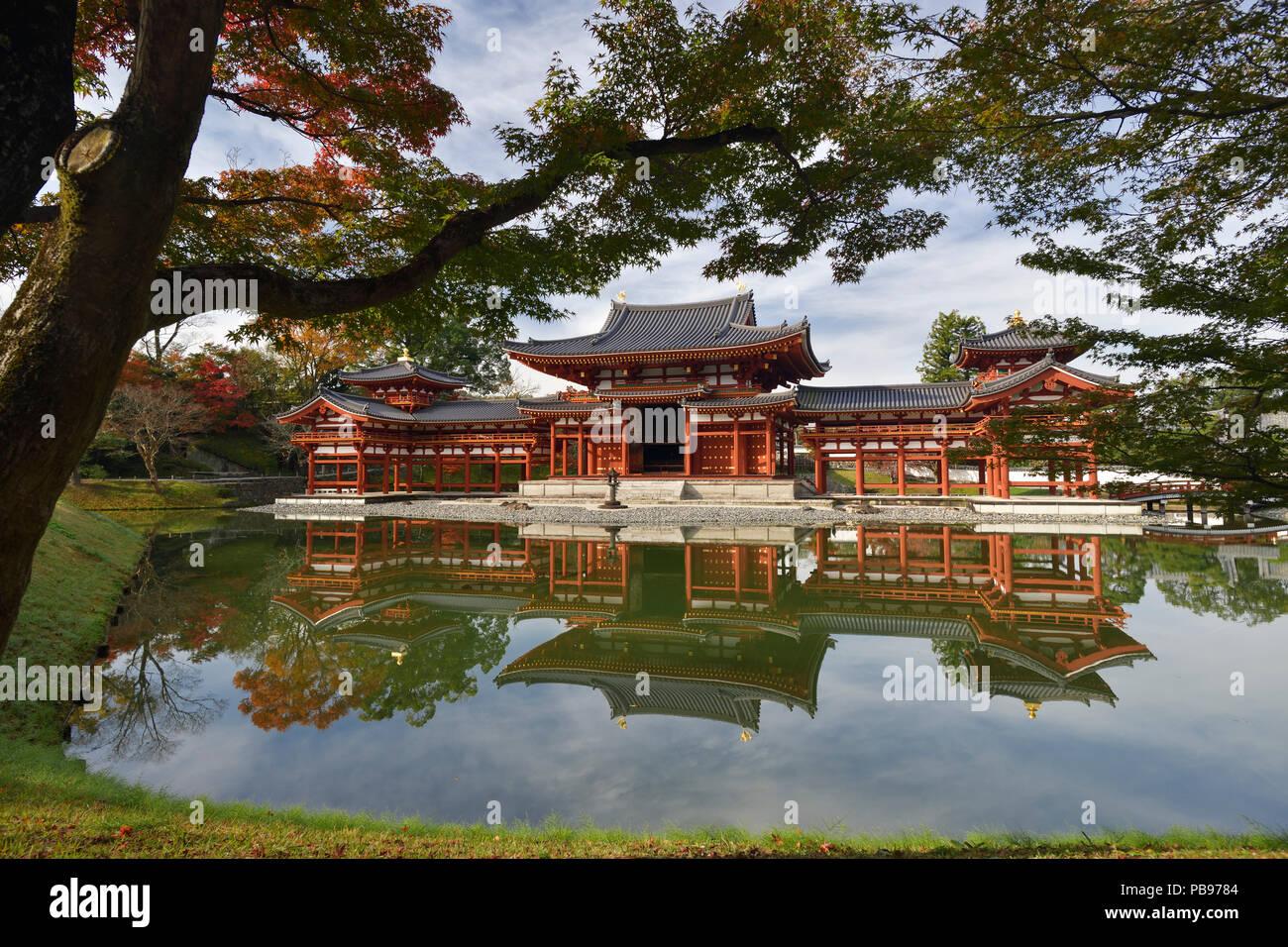 Peaceful autumn scenery of the Phoenix Hall, Amida hall of Byodoin temple on Kojima island of Jodoshiki teien, Pure Land garden pond on a bright sunny - Stock Image