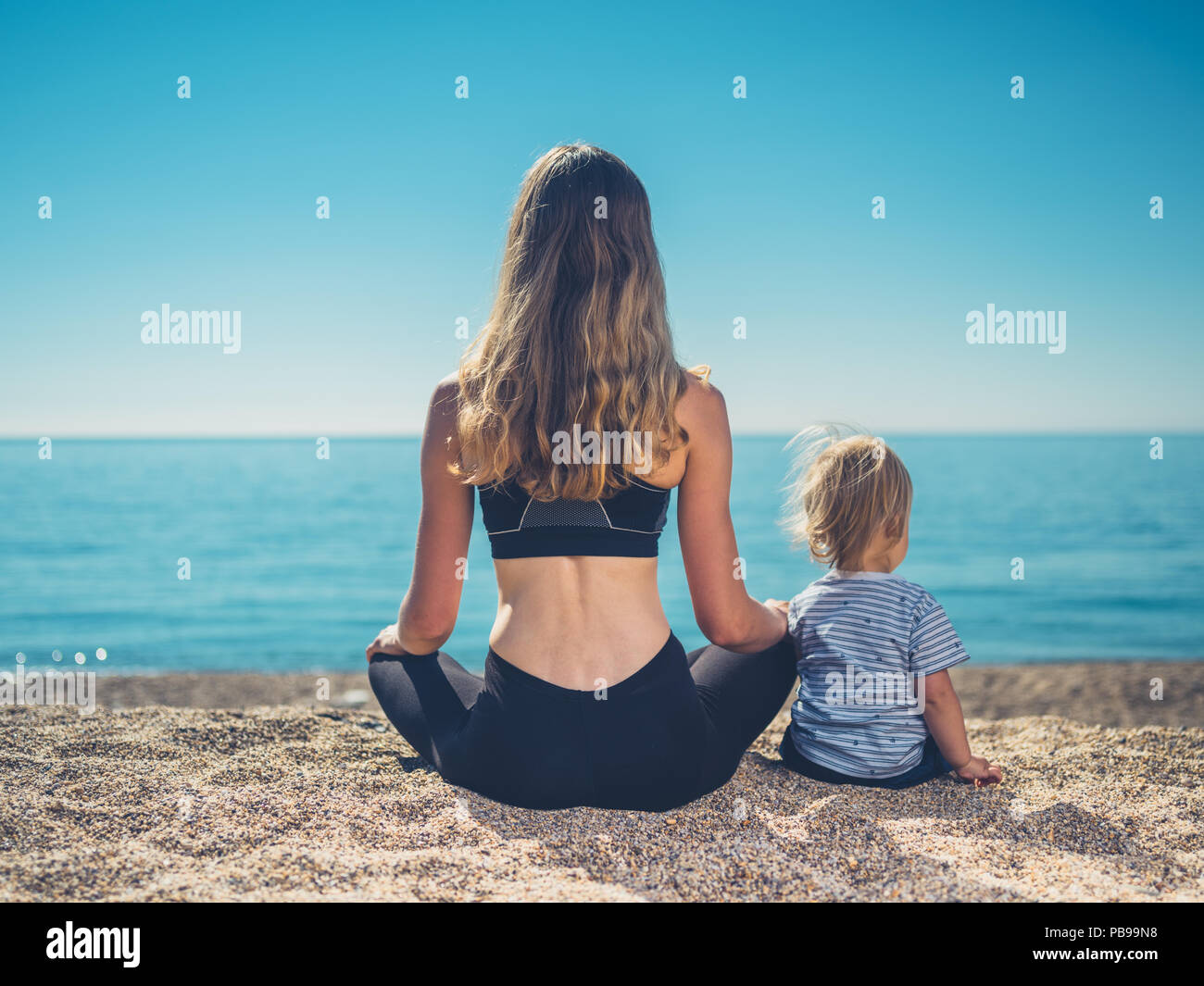 A young mother in fitness wear is relaxing on the beach with her toddler - Stock Image