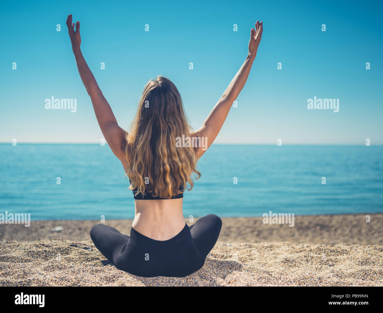 A young woman is sitting on the beach with her arms raised up in the air - Stock Image
