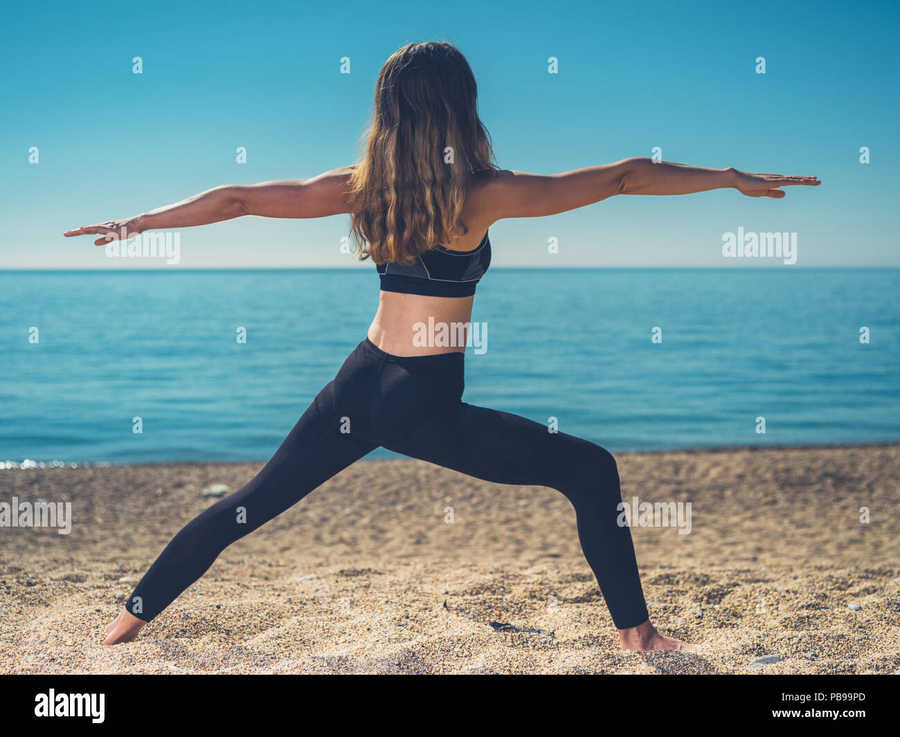 A young woman is in a warrior yoga pose on the beach in summer - Stock Image