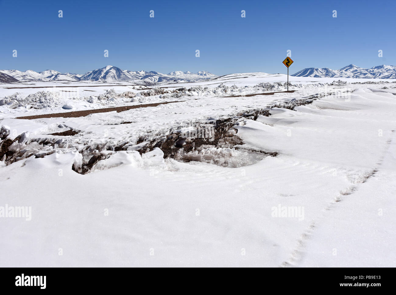 Snow-covered road through Atacama desert with road sign in front of Andes, Altiplano, Bolivia - Stock Image