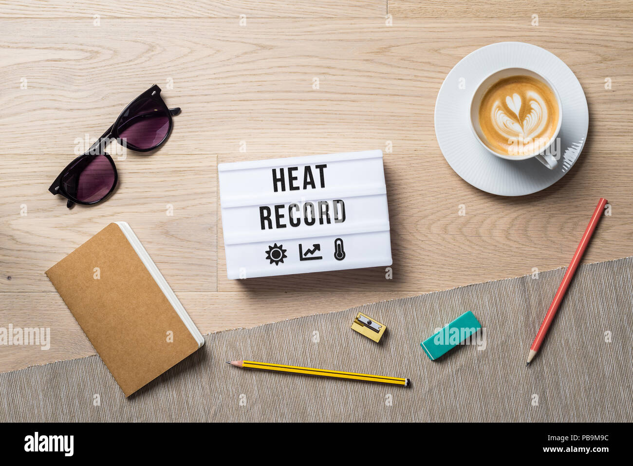 Heat record written on light box with sun and thermometer icons as flatlay from above of an office desk background with notebook - Stock Image