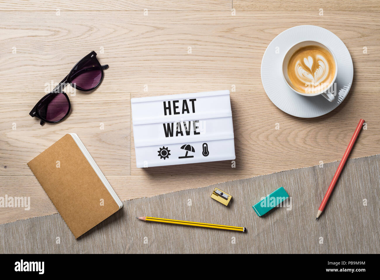 Heat wave written on light box with sun and thermometer icons as flatlay from above of an office desk background with notebook - Stock Image