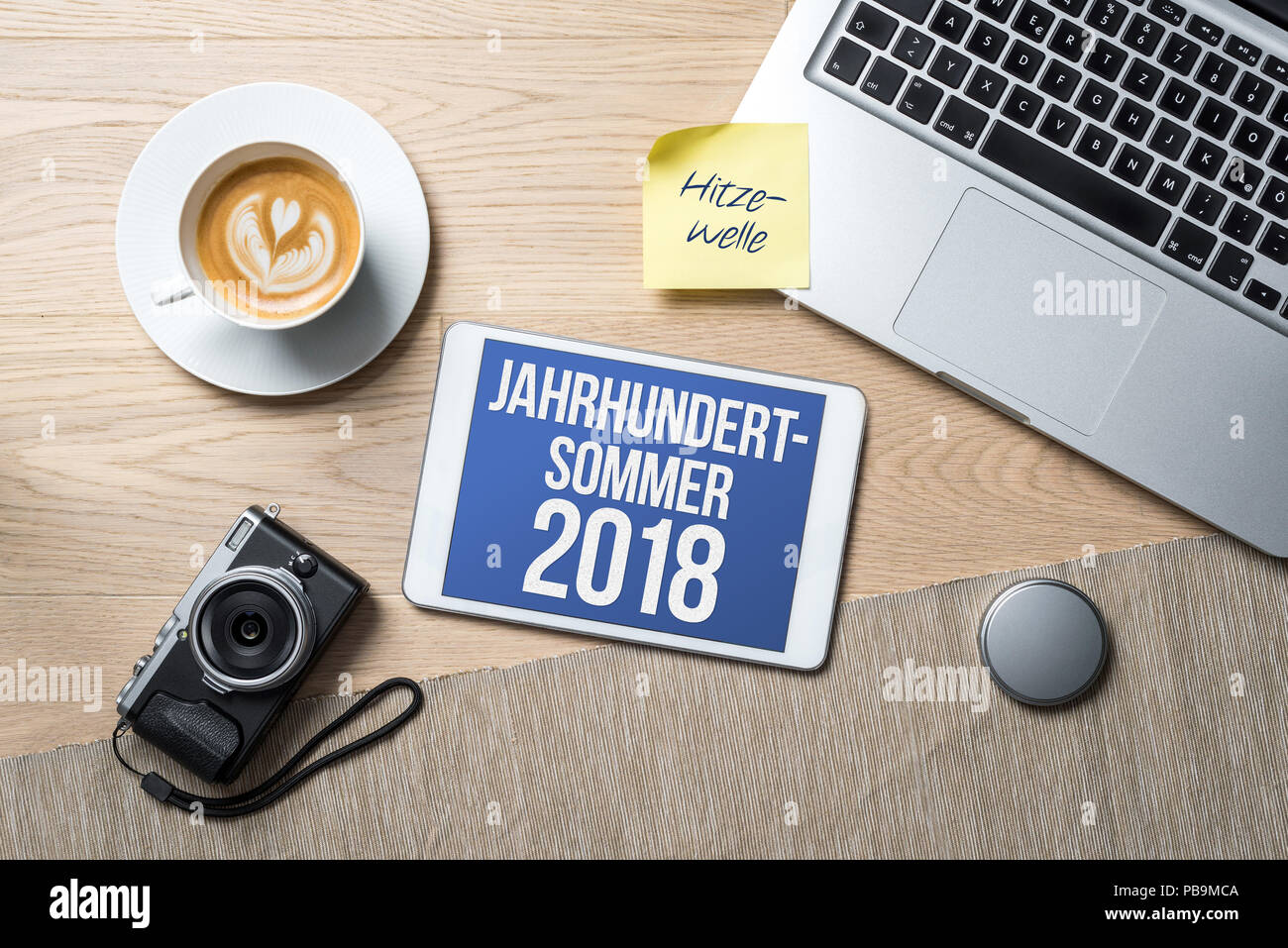 Jahrhundertsommer 2018 written in german on tablet meaning summer of the century and heat wave written on sticky note as flatlay from above of an offi Stock Photo