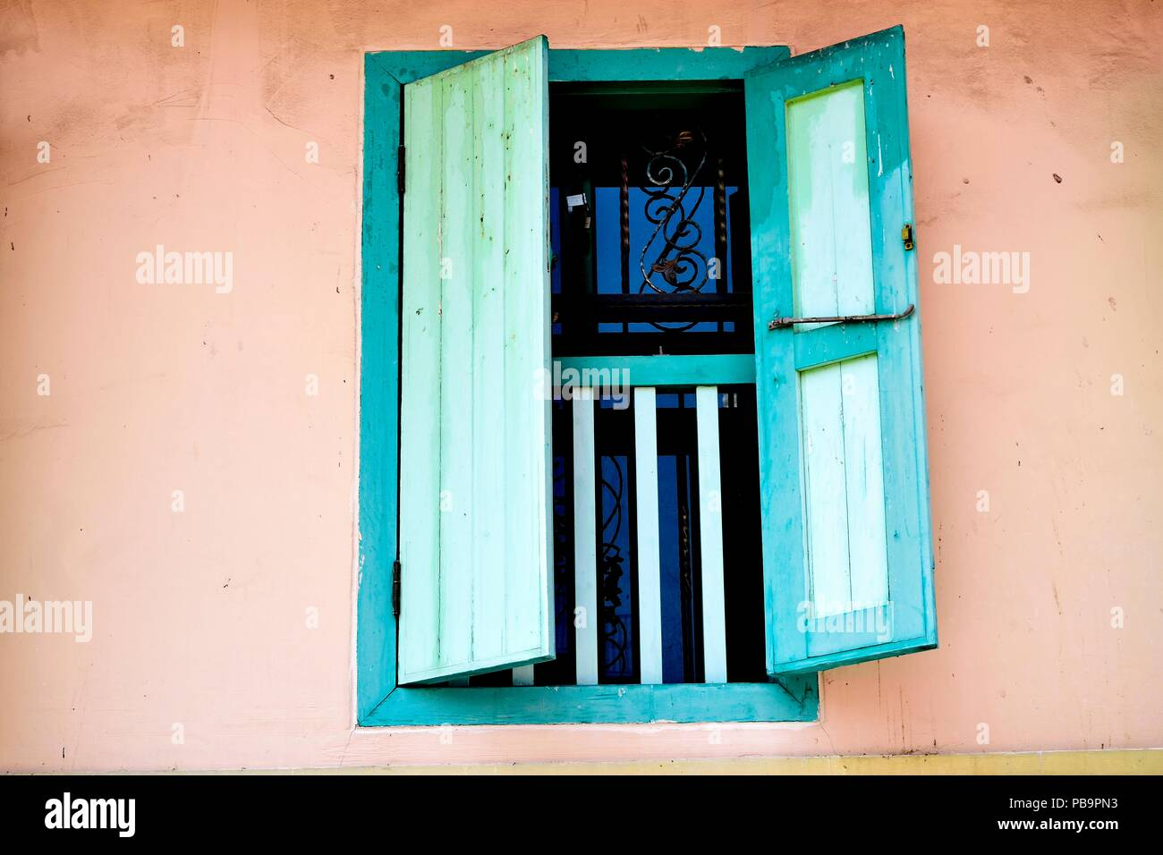 Perspective view of vintage window with open green antique wooden shutters as architectural background with space for copy. Stock Photo