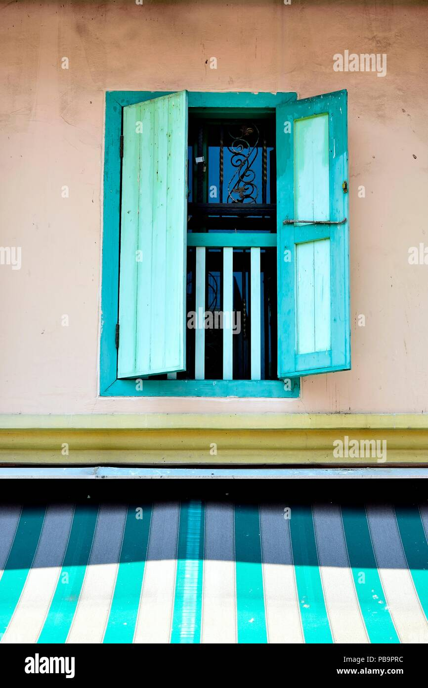Perspective view of vintage window with open green antique wooden shutters as architectural background with space for copy. - Stock Image