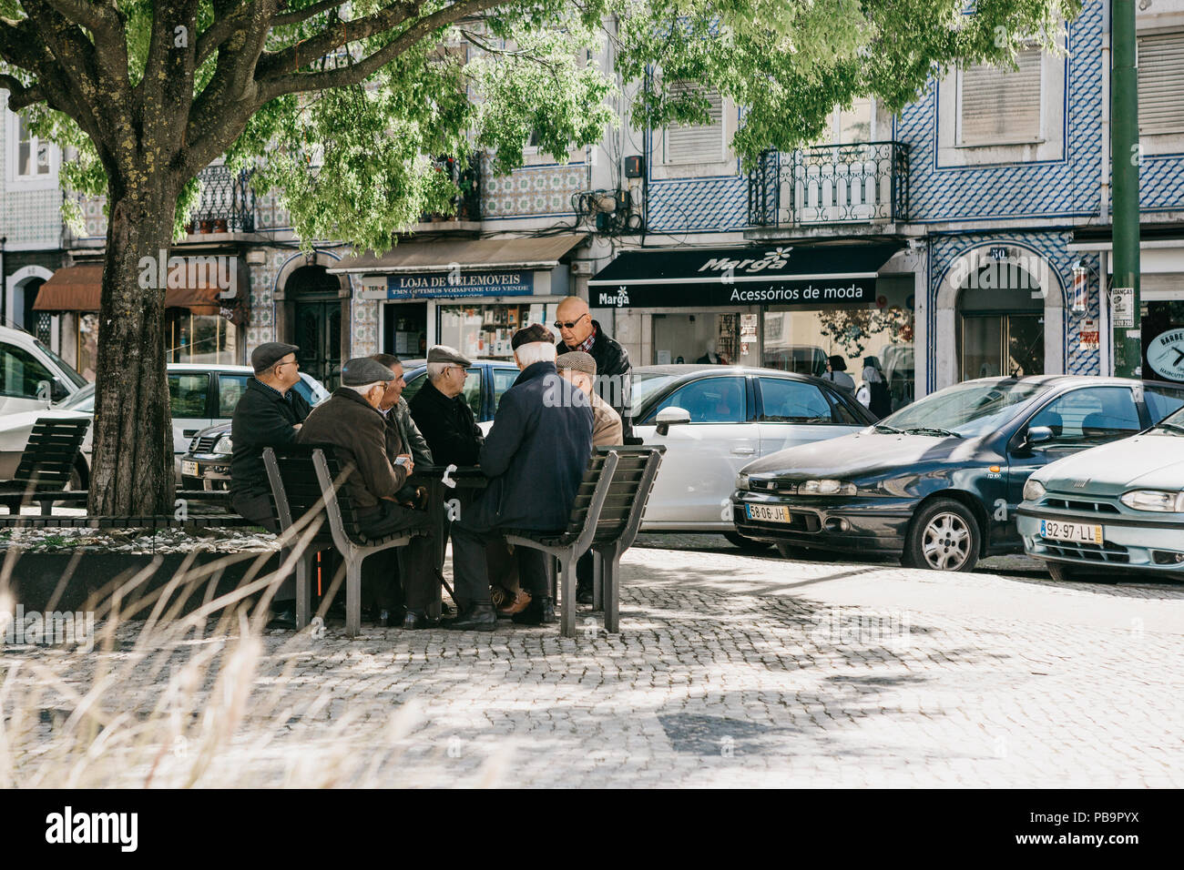 Portugal, Lisbon, 01 May 2018: Elderly Portuguese locals sit on the bench and communicate. - Stock Image