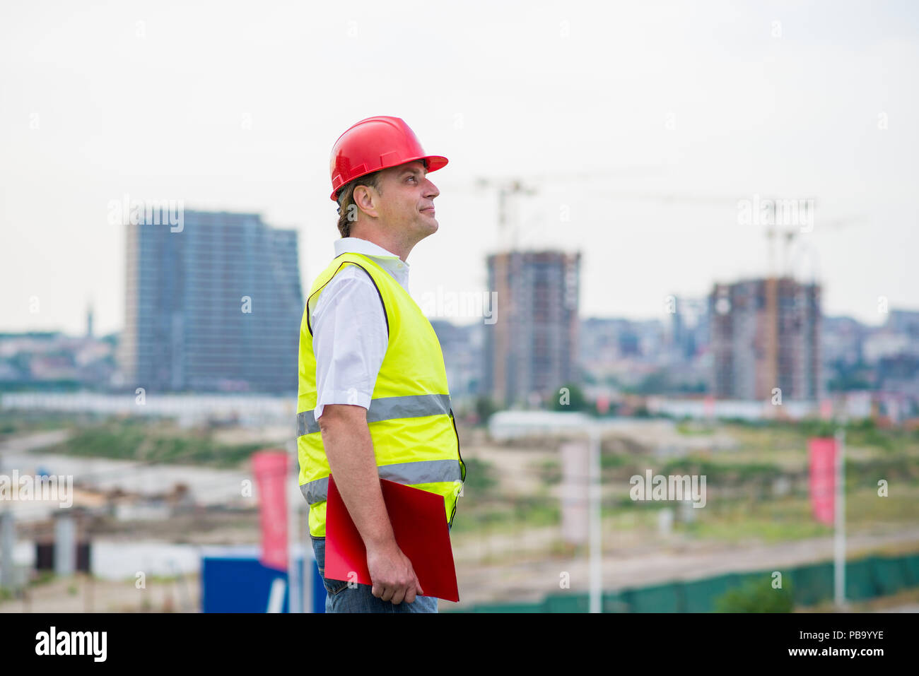Engineer on a construction site wearing yellow reflective west and red helmet with buildings and cranes in the background. Foreman on a building site - Stock Image