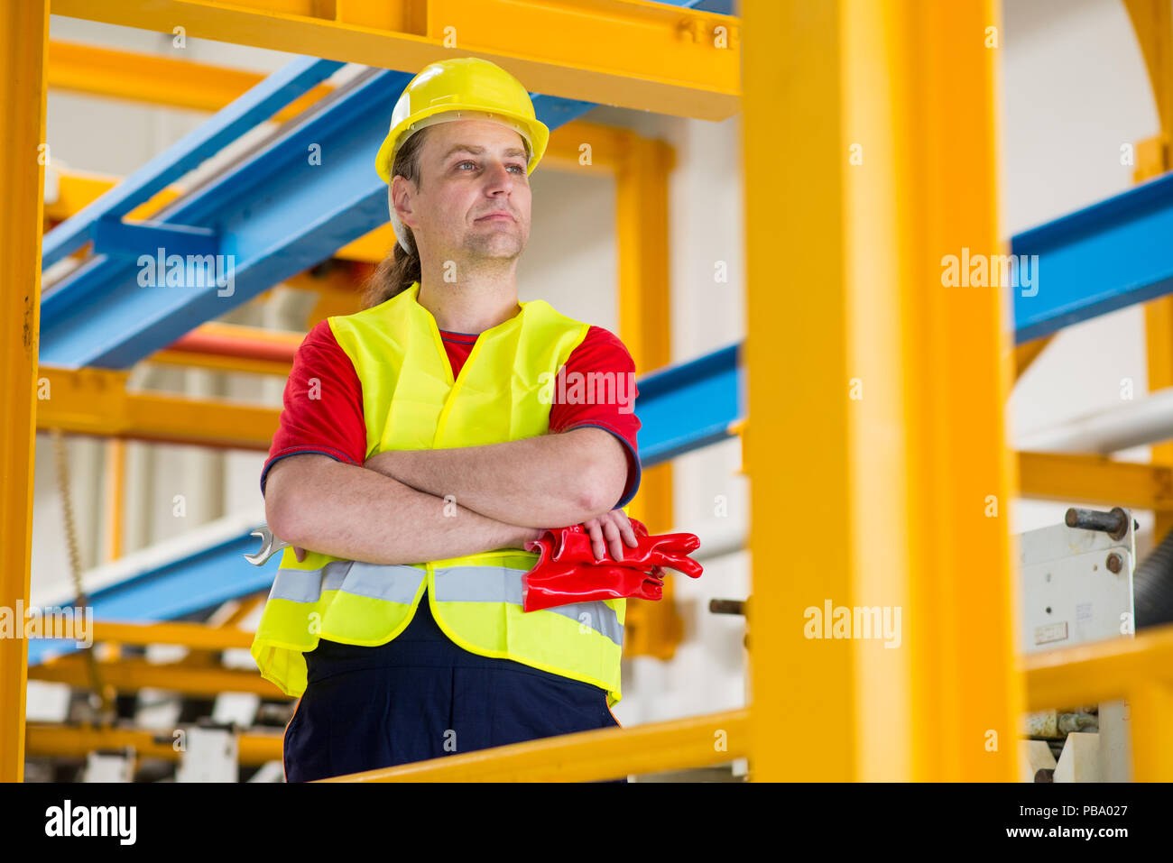 Factory worker in yellow reflective suit with yellow helmet with his arms crossed - Stock Image