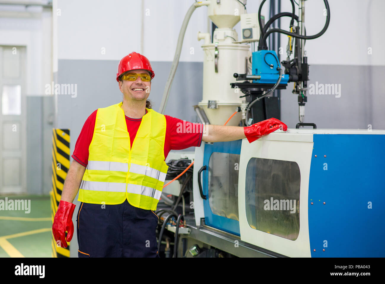 Smiling factory technician looking at a camera with one hand on a machine - Stock Image