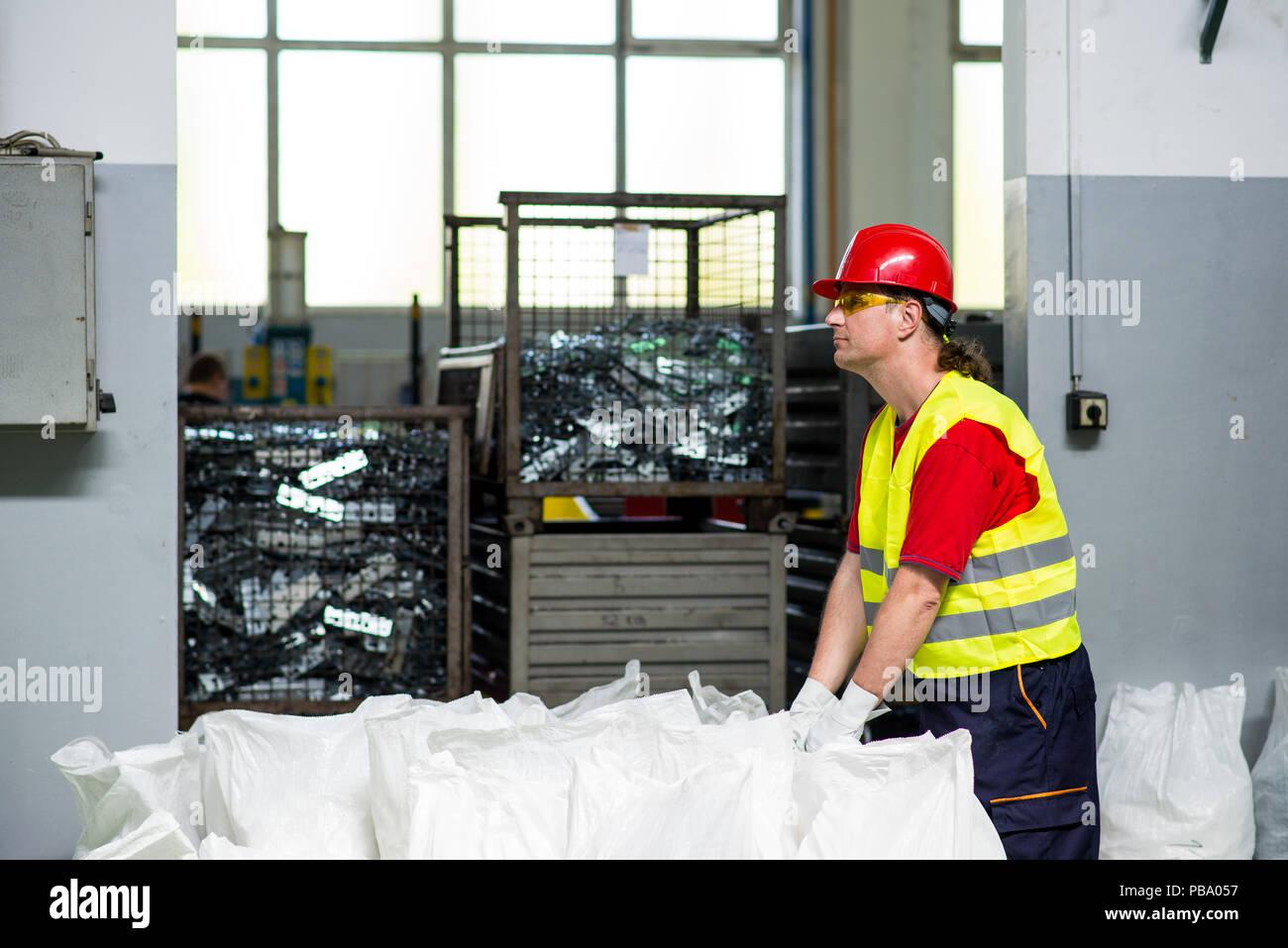 Factory worker standing beside loaded sacks - Stock Image