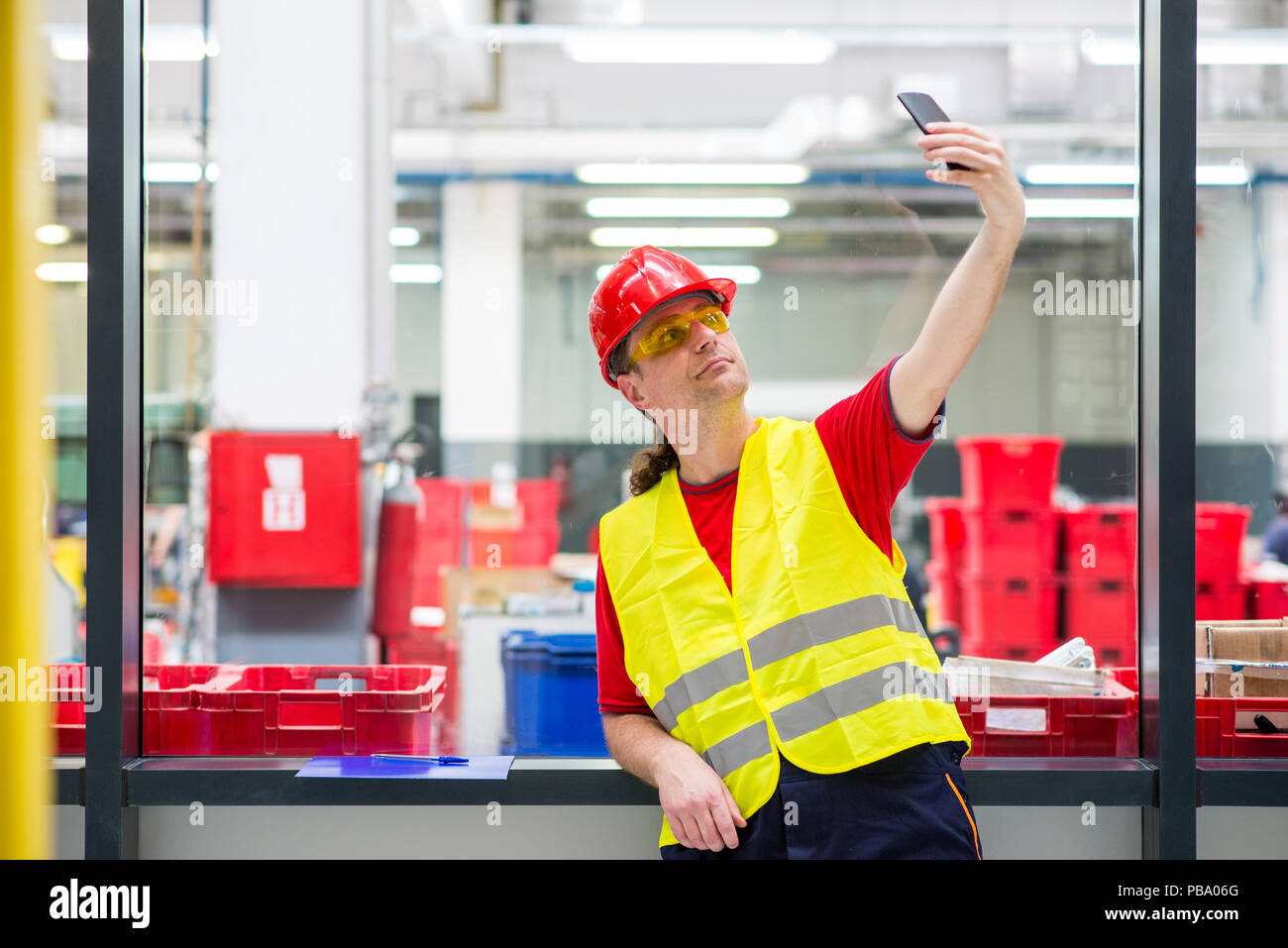 Factory worker taking selfie with his mobile phone inside the factory - Stock Image