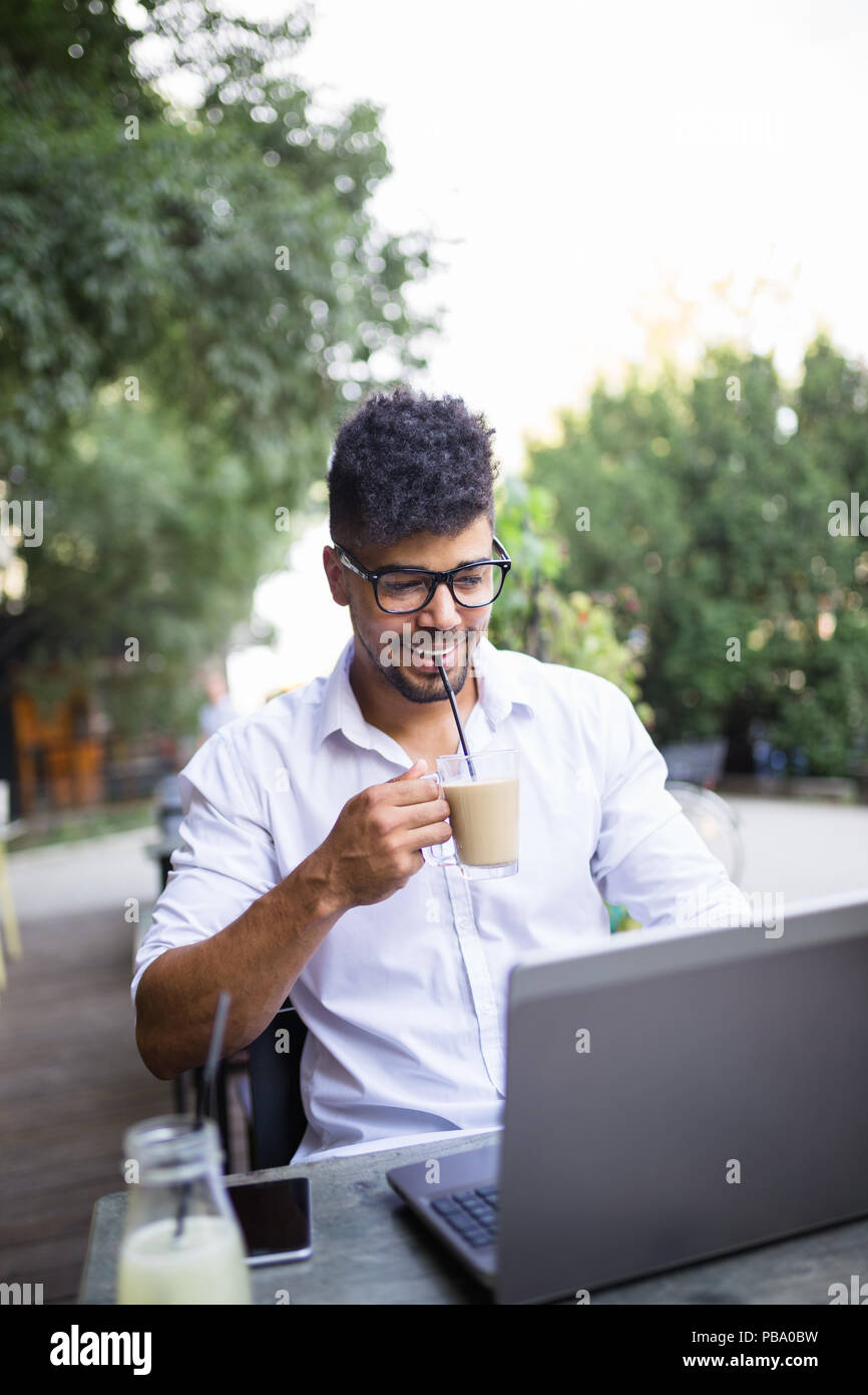 Young attractive afro American businessman sitting in cafe bar, drinking coffee and doing some work on laptop. - Stock Image