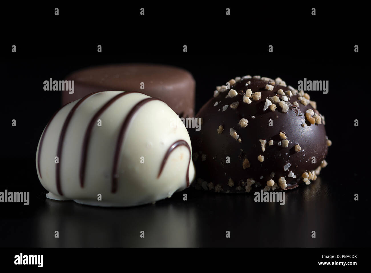 Close up of three chocolate bonbons, white, dark and milk chocolate. Sweet, calorie-rich and energy-rich food with unhealthy and fattening qualities - Stock Image