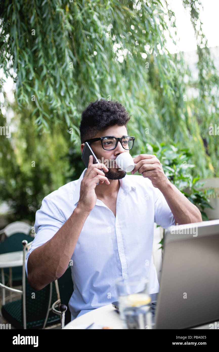 Young attractive afro American businessman sitting in cafe bar doing some work on laptop and taking on mobile phone. - Stock Image