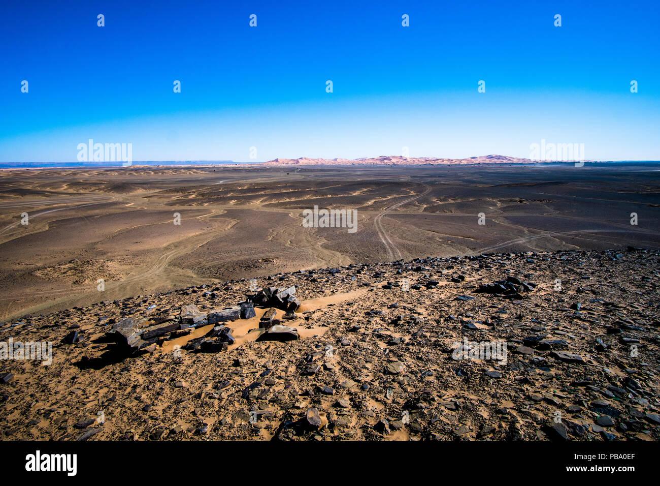 Volcanic black basalt terrain in Sahara desert in Morocco - Stock Image