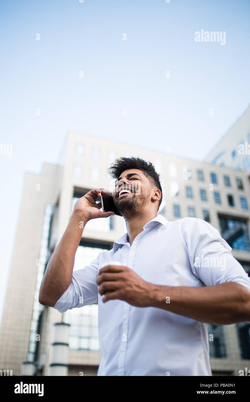 Young handsome Afro American man standing in front of huge modern business building, smiling, holding coffee to go and talking on mobile phone. - Stock Image