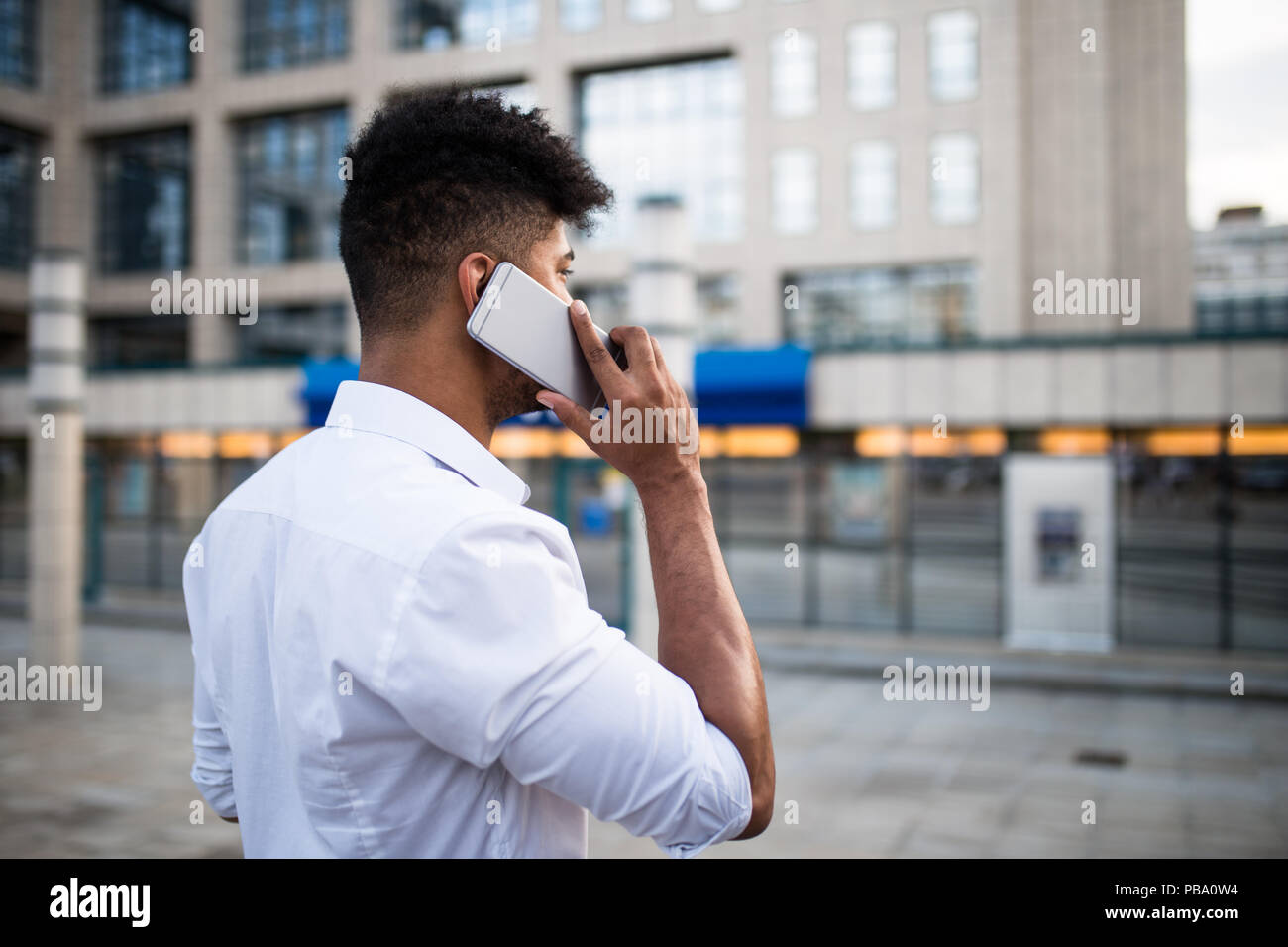 Young handsome Afro American man standing in front of huge modern business building; smiling and talking on mobile phone. Stock Photo