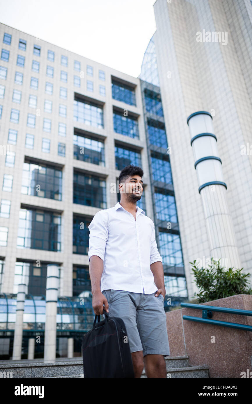 Young handsome Afro American man  in front of huge modern business building. - Stock Image