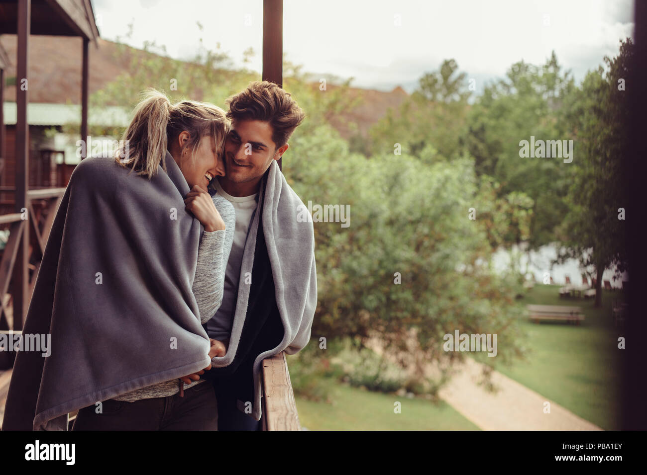 Loving man and woman standing in their hotel room balcony wrapped in blanket. Romantic couple in a blanket standing together on a winter holiday. - Stock Image
