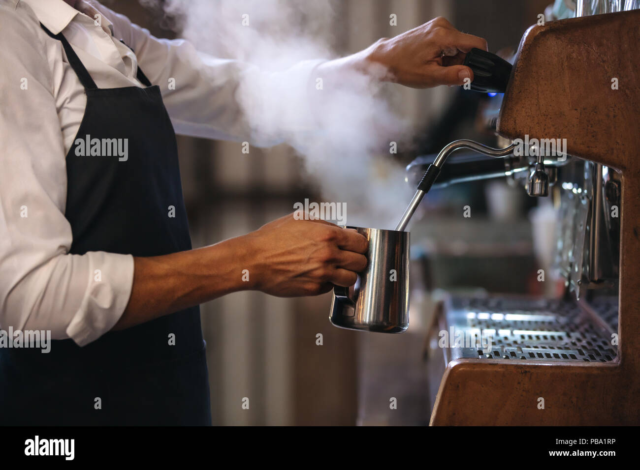 Coffee shop worker preparing coffee on steam espresso coffee machine. Cropped shot of man working in coffee shop wearing an apron. - Stock Image