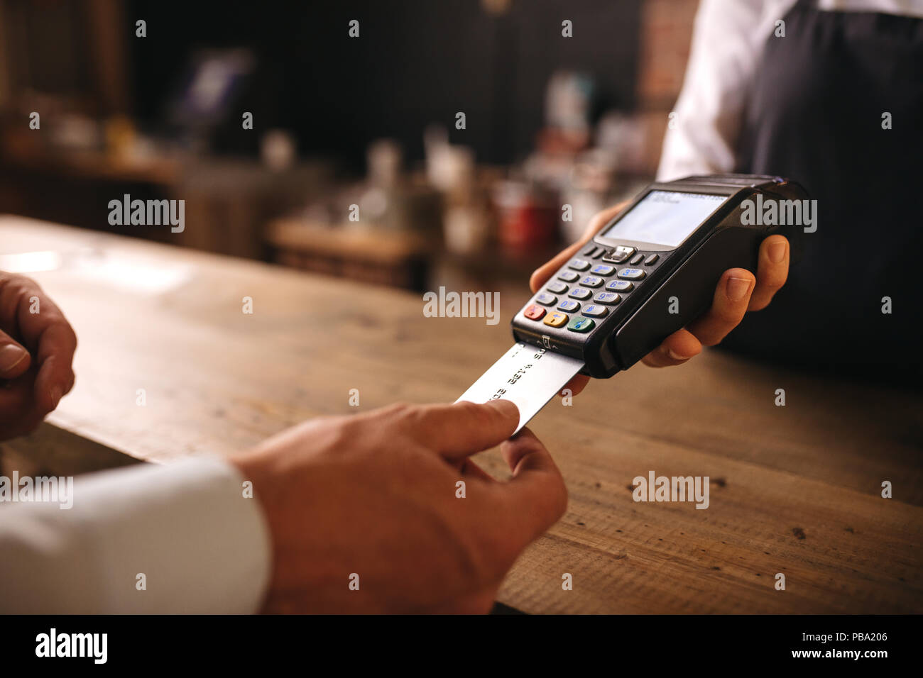 Customer inserting his credit card in the machine to payment at cafe. Customer paying for their order with a credit card in a cafe, with bartender hol - Stock Image