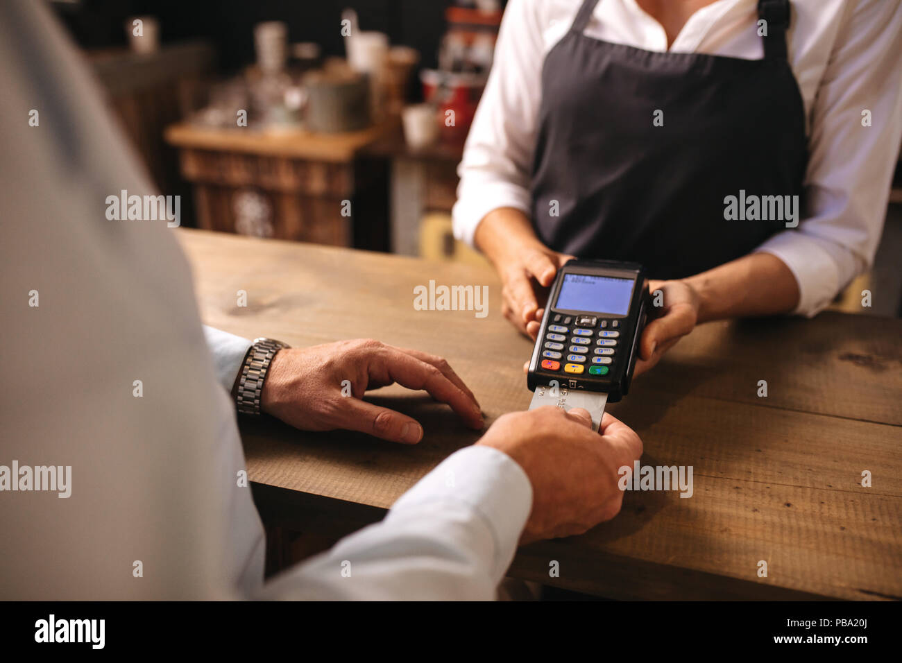 Cropped shot of male customer paying for coffee by credit card at cafe. Woman barista holding a credit card reader machine with man doing payment on c - Stock Image