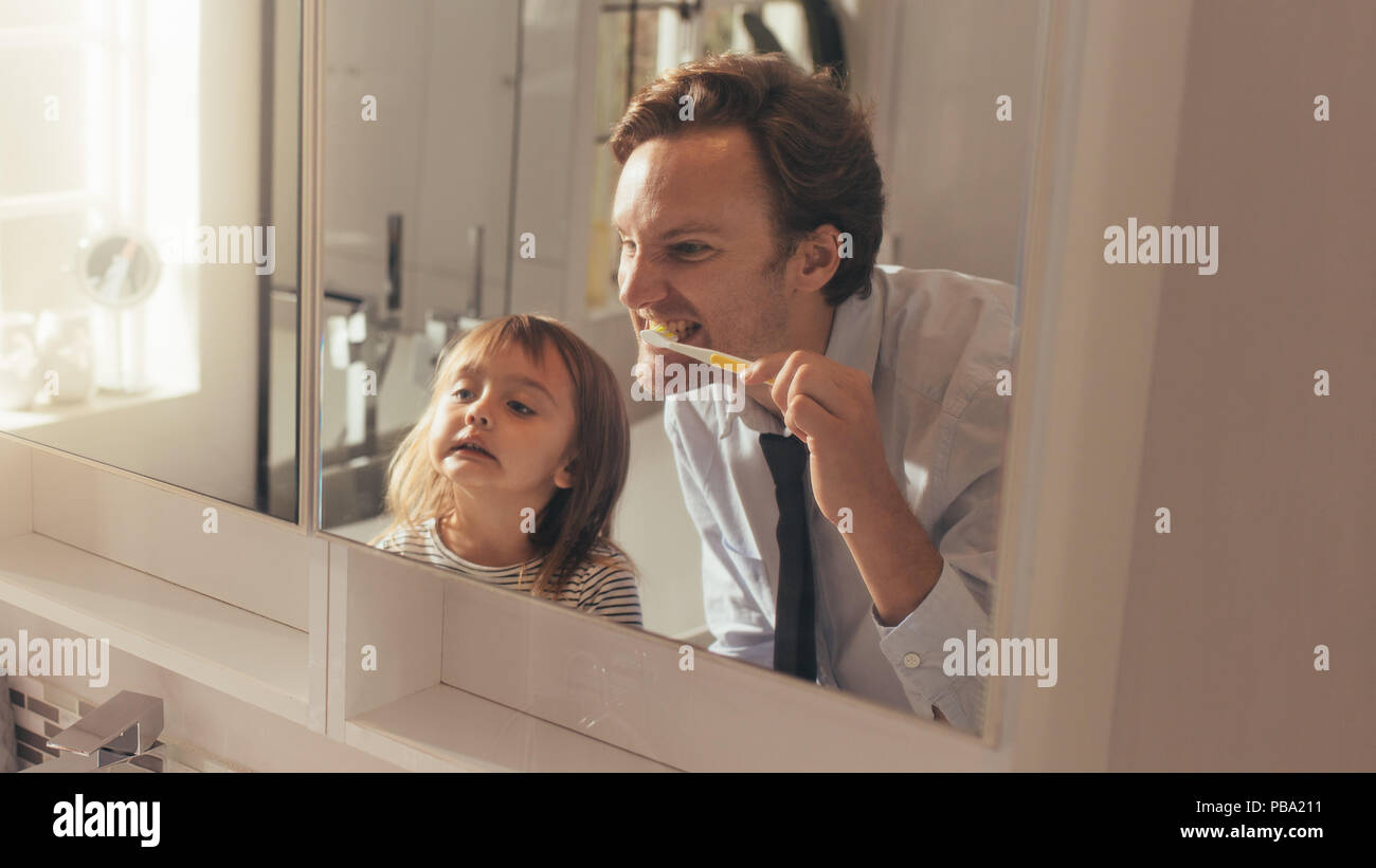 Man brushing his teeth looking into the mirror standing in bathroom while his daughter looks on. Man teaching his daughter how to brush teeth. - Stock Image