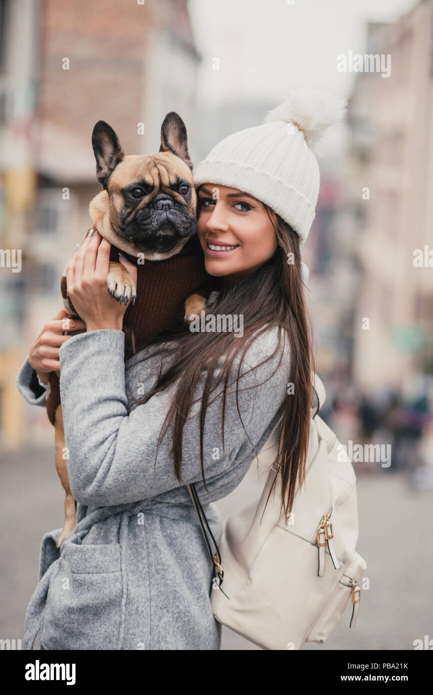 5c47967efcc9 Beautiful brunette woman holding her adorable French bulldog. - Stock Image