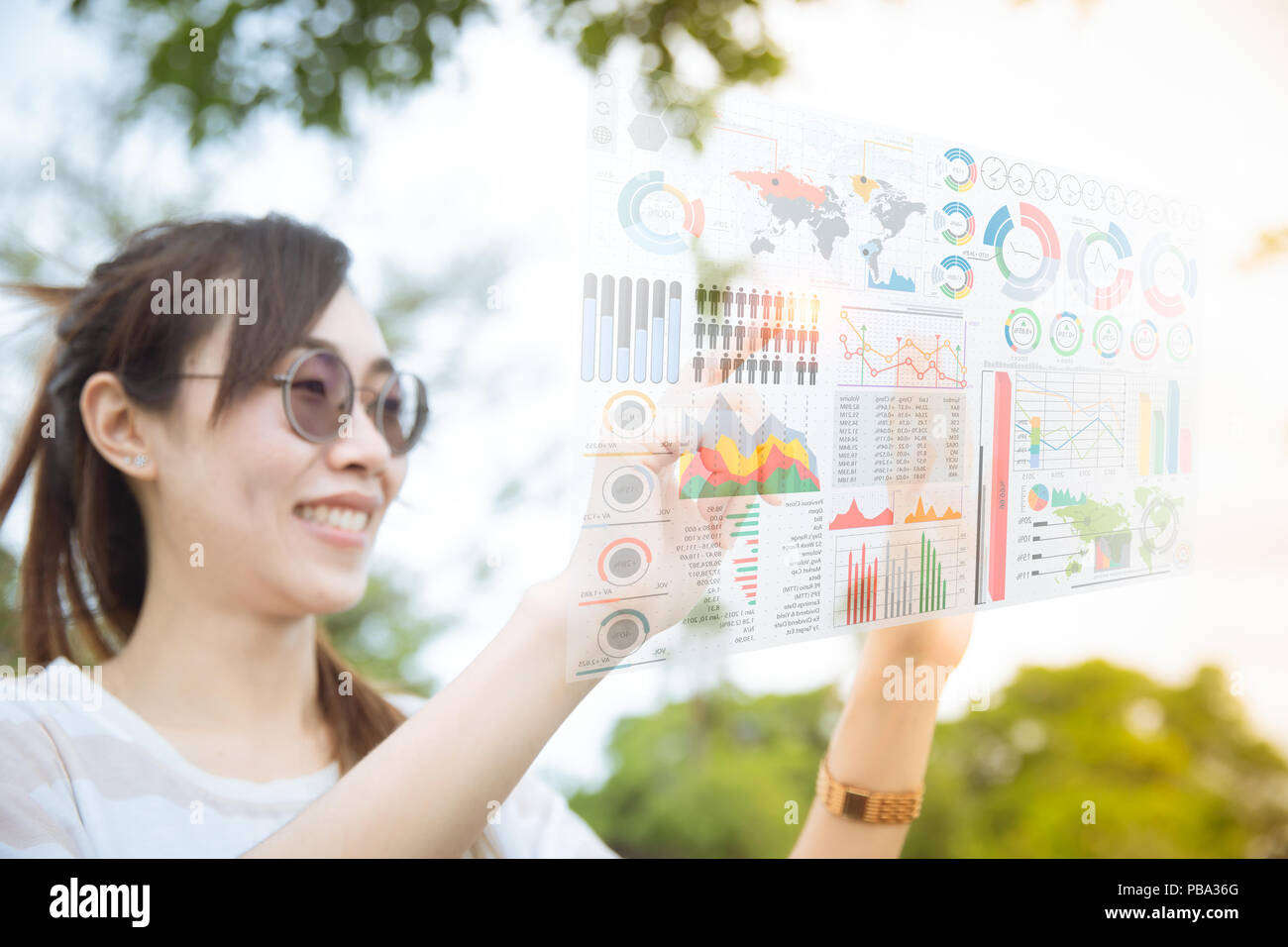 Asian chinese girl using advance technology of computer hologram air screen display mix media business information data chart outdoor Stock Photo