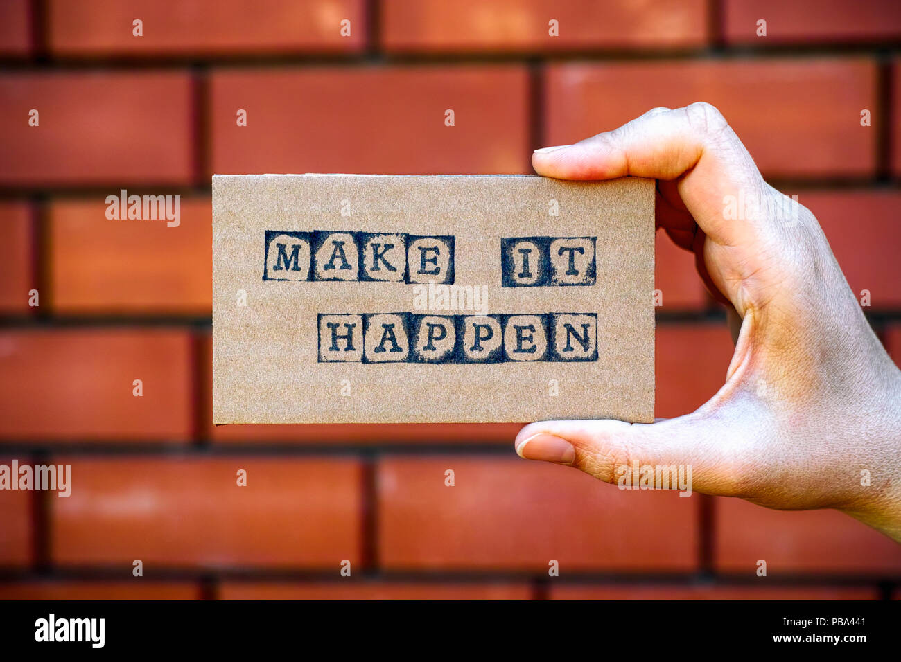 Woman hand holding cardboard card with words Make It Happen made by black alphabet stamps against brick wall background. Stock Photo