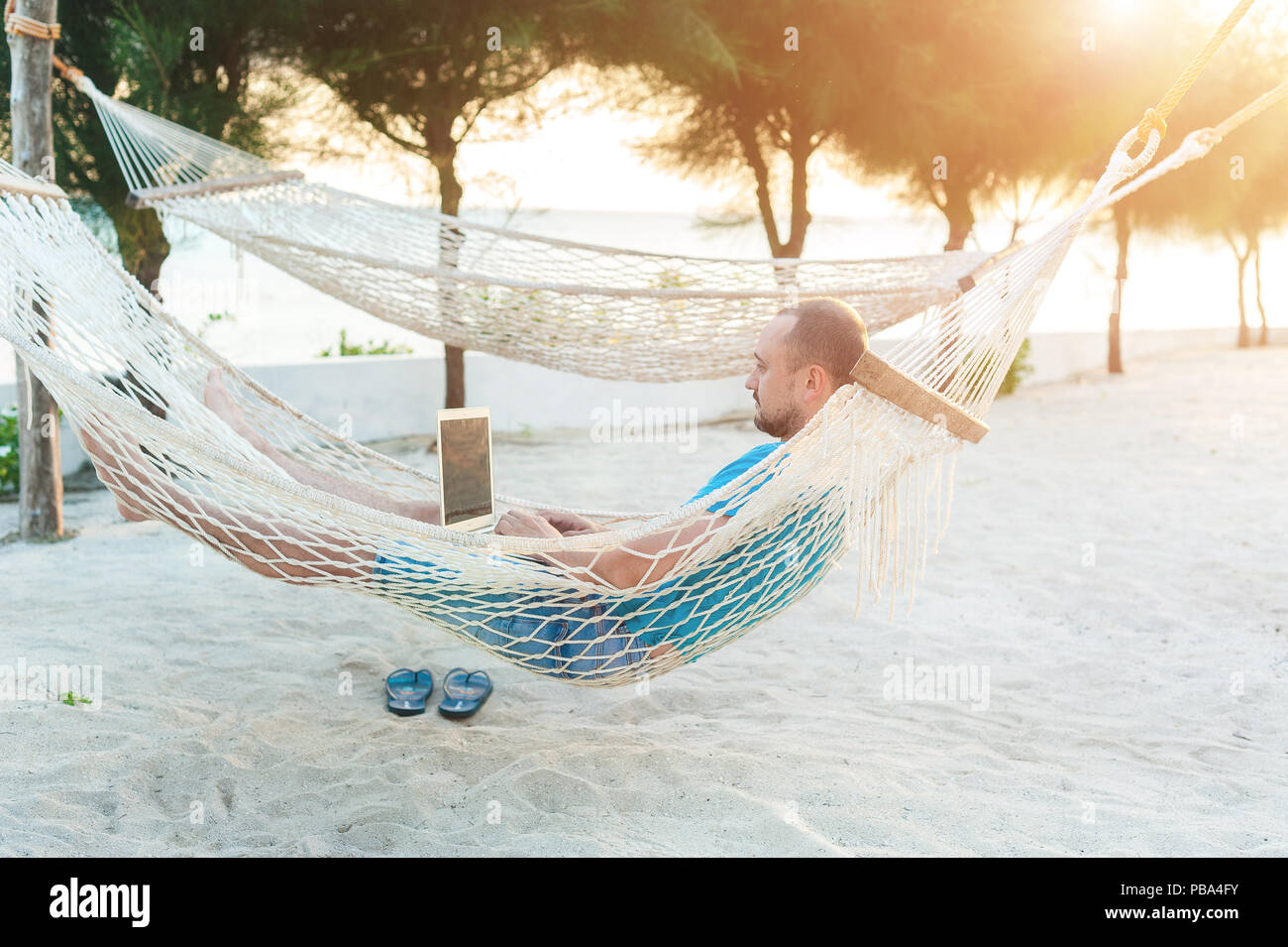 A man with a beard lying in a hammock with a laptop. Remote work on the beach - Stock Image